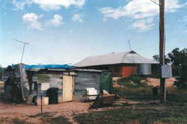 A humpy retained as a past lifestyle symbol in a rural town in western New South Wales in 1999 with an ATSIC house behind. Photograph Paul Memmott.
