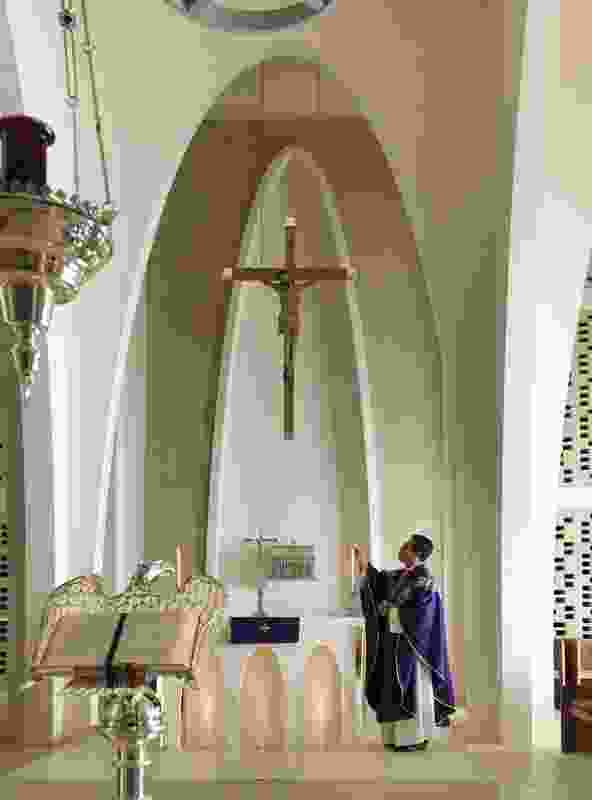 An arched column creates a double-height vaulted space, framing the altar.
