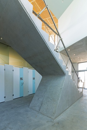 The interior colour palette draws from the bricks cladding the exterior, while this solid concrete stair is reminiscent of the angled massing of the building itself.
