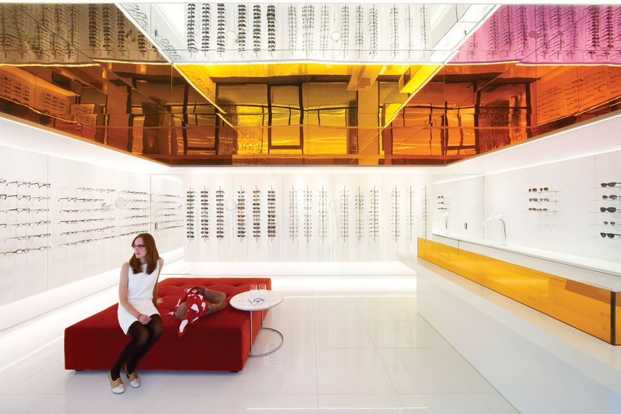 The optometry store's trademark is it's colourful mirror and glass canopy which reflects colour and light around the space.