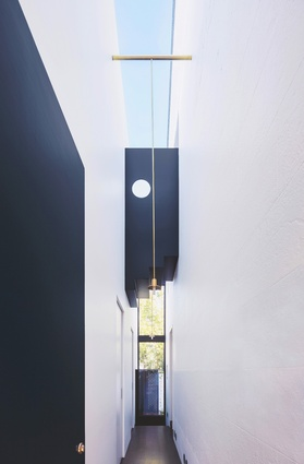 A Peter Zumthor brass light is suspended high in the entry passage, with the sky seen through the clear glass ceiling above.