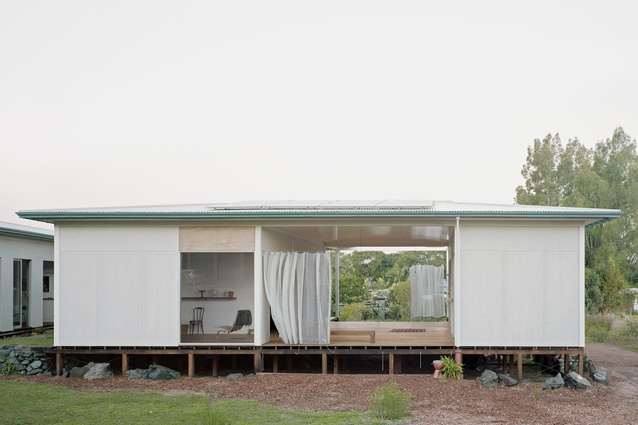 The house is positioned centrally on its wide suburban site and its portico is open to the street save for a shadecloth curtain, weighted with locally sourced metal chains.