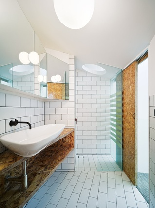 The bathroom has a lowered ceiling to be proportional to the dimensions of the room in plan. A playful circular cut-out above the shower is featured.