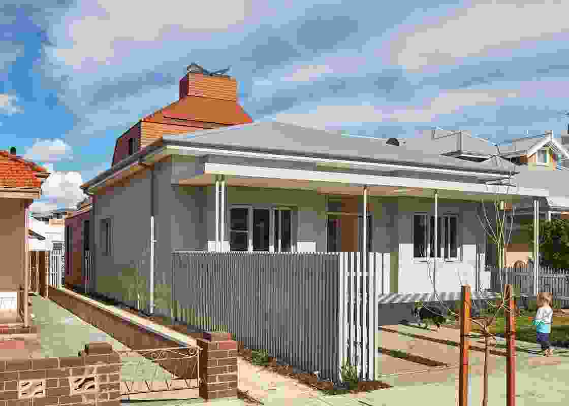 The 1960s concrete verandah and facade are painted in a unifying grey tone, drawing attention to the addition.