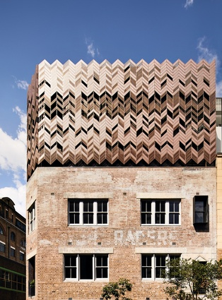 The copper screen facade provides shade and natural ventilation and appears like a crown on the building.