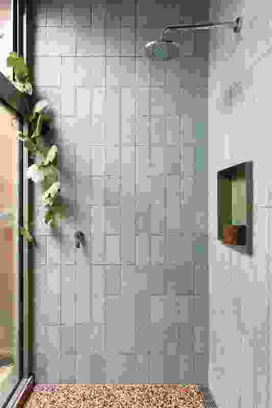 Pale green tiles in the shower recess contrast with the terrazzo floor.