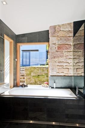 The bathroom window frames a garden view.