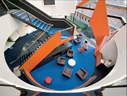 Looking down into the main stair void, through which an orange ribbon twists.