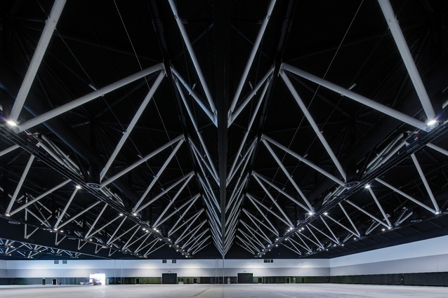 There are two levels of exhibition halls: the lower halls ordered by major structural columns and the upper halls free of structure, supported by cambered steel trusses.