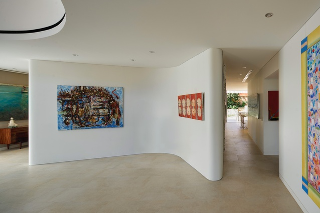 "A ""wishbone"" feature housing a discreet study room helps to divide the lower level into formal and informal spaces. Artwork (L-R): Ann Thomson; John Firth-Smith."