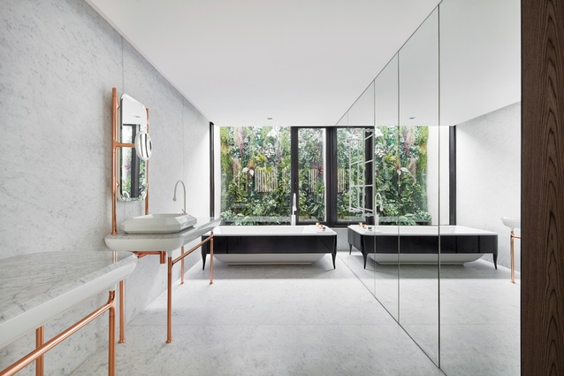 The bathroom's mirrored walls and views to greenery create an inviting atmosphere, the marble surfaces and copper-finished fittings adding a touch of opulence.