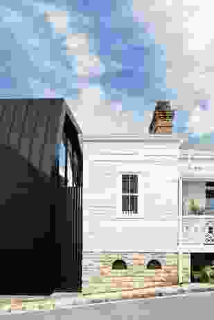 Inky black metal cladding combined with painted white weatherboard makes for an eclectic yet unified palette.