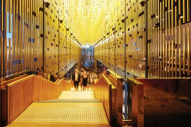 Beneath curtains of gold anodized aluminium tubes, the staircase ascends to the main theatre.