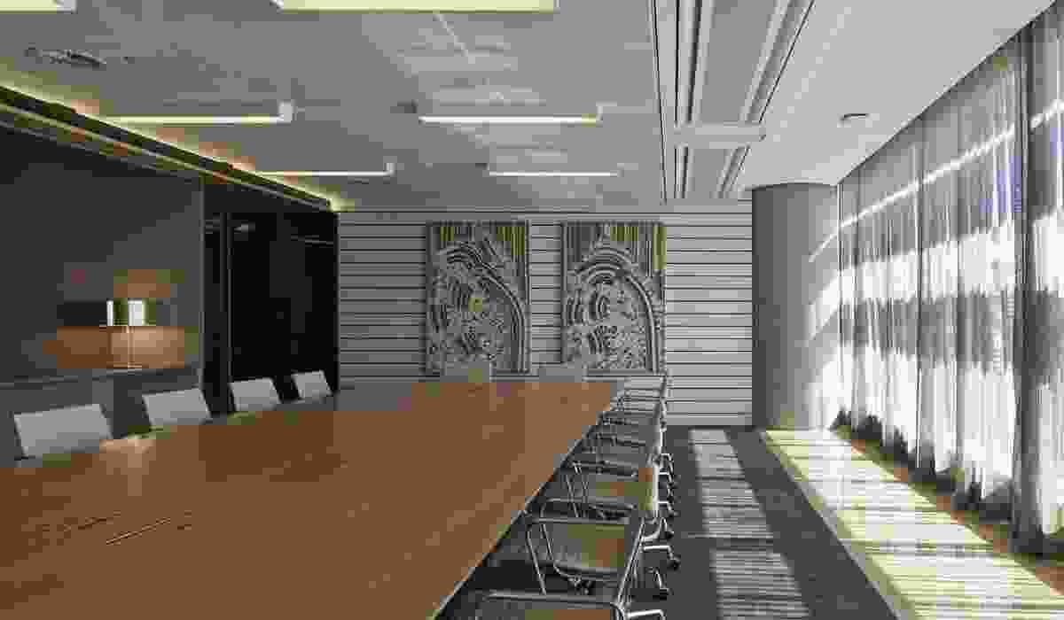 Formal meeting rooms feature artwork and honey-gold tones.