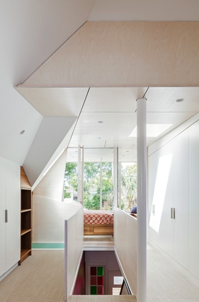 Previously an attic, the gallery space at the top of the stairs is shaped by planes of plywood