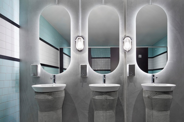 Bathrooms mix modern and art deco-inspired elements with ceramic basins on stout concrete pillars.