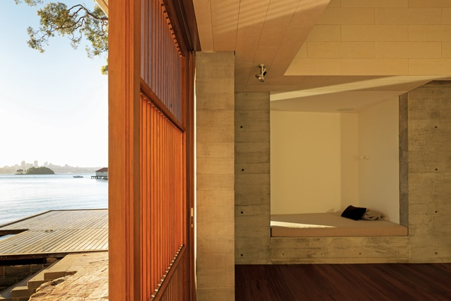A day bed is carved out of the stone wall, allowing appreciation of the view of the bay via a vertical slot window.