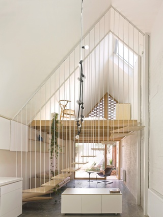 A sculptural suspended stair acts as a porous barrier between the dining and living rooms.