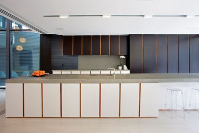 A large island bench topped with polished concrete runs the length of the kitchen.