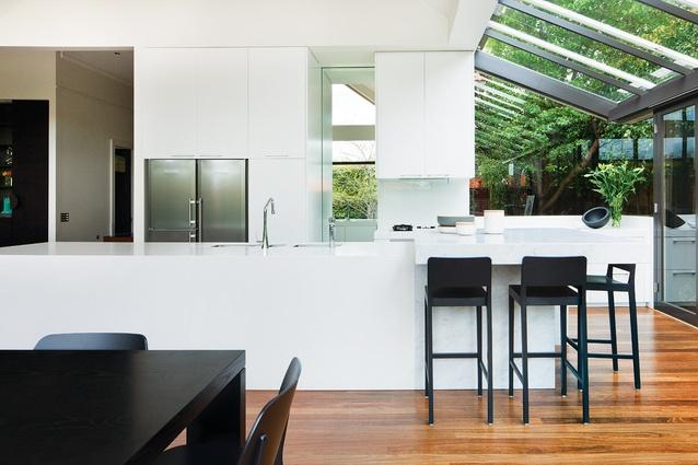 A fresh, white kitchen commands views of the backyard.