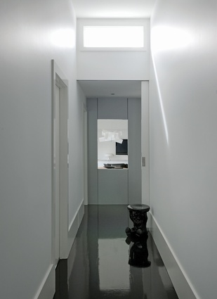 Dark-stained timber floors contrast with white walls in the entry hall.