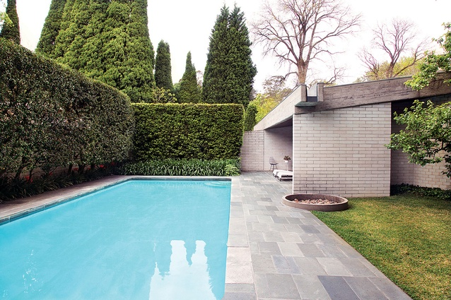 A wall projects outside the building separating the pool area from the entry.