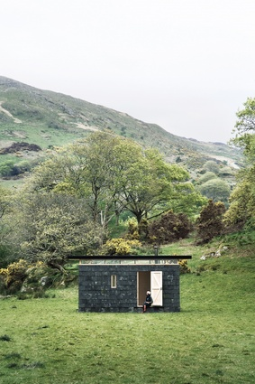 Slate Cabin, a writer's retreat in Wales, is a reductive black box anchored to the ground, providing protection and respite to visitors.