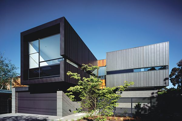 The building form contrasts solid mass with walls of glass.