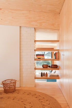 Glazing behind the bookshelf lets natural light bounce beautifully off the hoop pine lining.