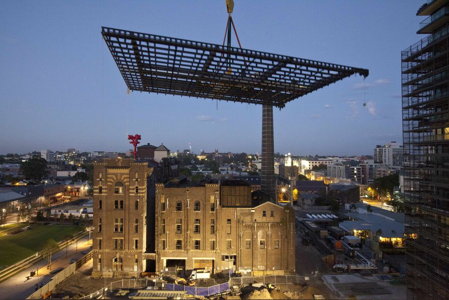 The heliostat frame rises under dawn light at One Central Park, Sydney.