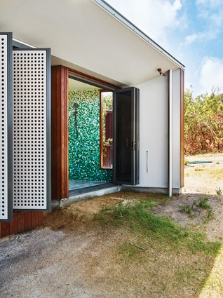 A colourful mosaic-tiled indoor/outdoor bathroom makes the most of its remote location.