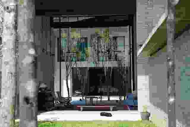 花园壳住宅-客厅的外壳有助于屏蔽从高架轨道到后方,同时使客厅在前花园和中间庭院之间的亭子