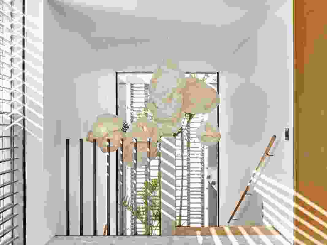 A pendant adds drama to the stairwell, which offers garden views through its full-height windows.
