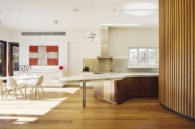 A curving timber wall leads to the light-filled kitchen and living area.