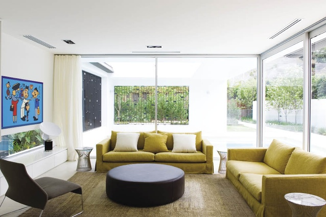 """The living room looks out onto the outdoor pool """"room"""" and beyond into the garden."""