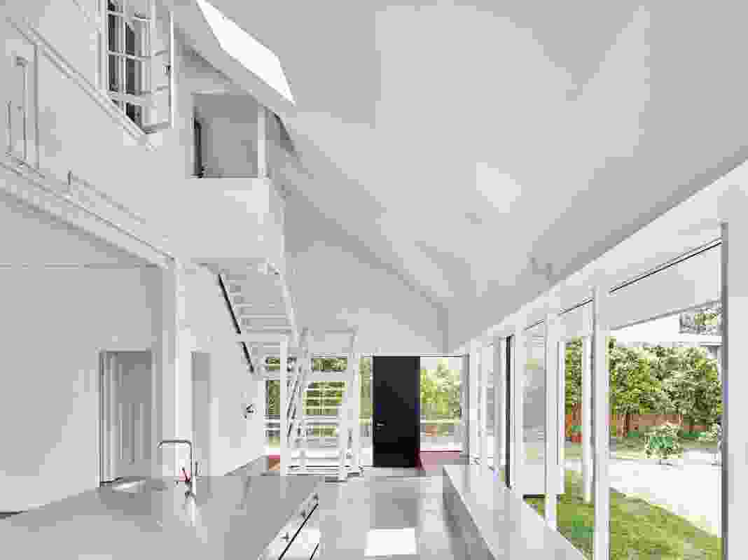 The original external stair is now encompassed by a new double-height atrium that runs the entire width of the house.