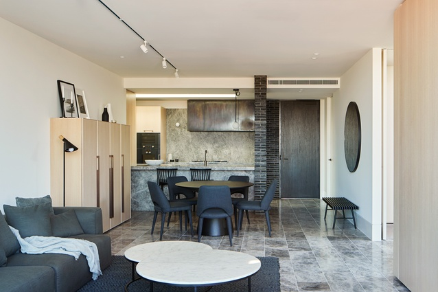 The apartment interiors comprise a series of independent joinery elements clad in grey stone, bronze or timber veneer.
