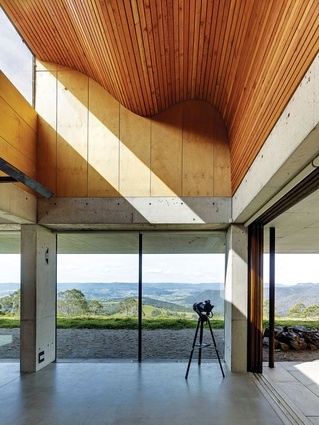 A rolling, double-height ceiling of battened  timber draws light into the living area.