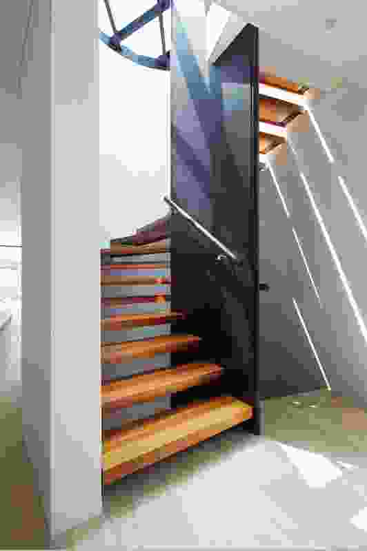 Sunlight filters through the open risers of the central horseshoe- shaped staircase in each home.
