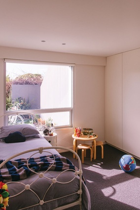 In the new living space, two bedrooms for the clients' boys are accessed via a short hall concealed behind a sliding panel.