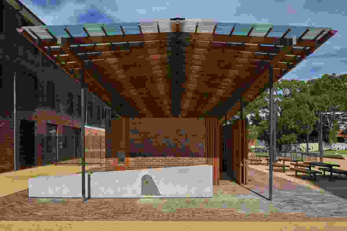 The original slate roof of the operating block has been extended and twisted upwards into a translucent roof of colourful polycarbonate shingles that now provides a sheltered outdoor area for public activities and events.