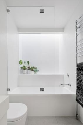 A stark, white bathroom reflects the house's crisp palette and minimalist design language.
