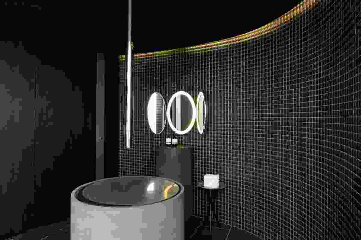 The bathroom contains a series of circular shapes, with black steel basins.