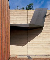 Folded metal, clipped onto the rammed-earth wall, defines the entry.
