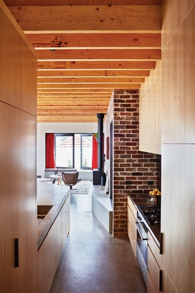 Recycled red bricks from the existing dwelling make a bold statement in the kitchen/living area, tying old and new elements together.