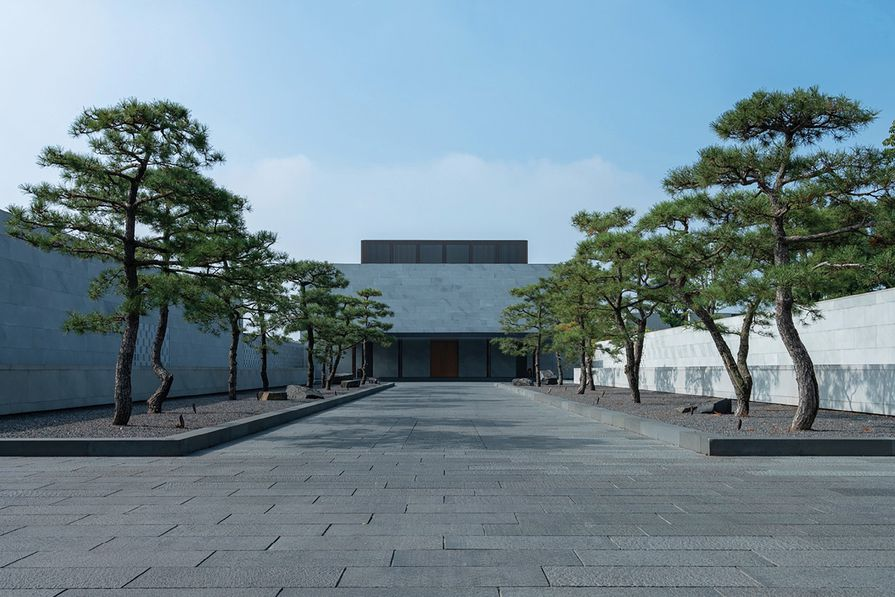The ensemble forming the resort's main entrance – a door set in a severe stone-clad box, approached along a tree-lined axis – has a temple-like quality.