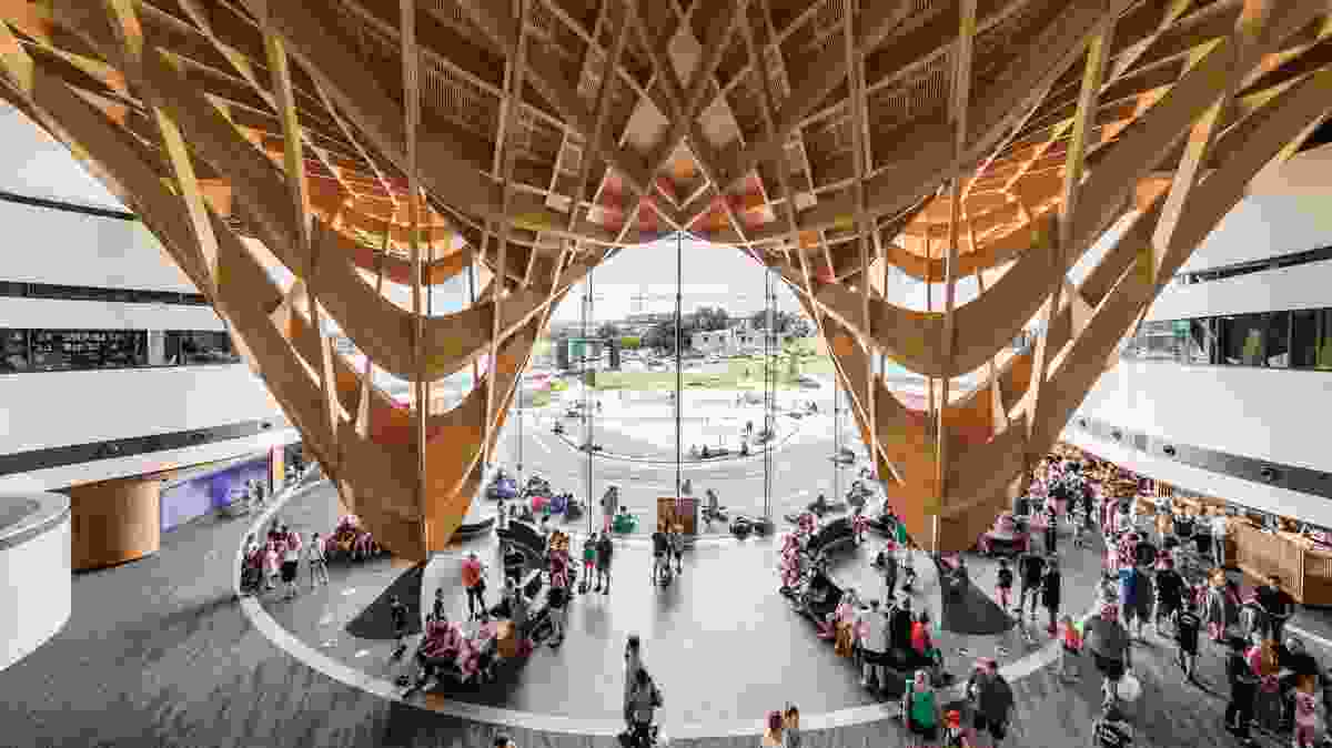 Beneath the roof, the woven timber structure is pulled dramatically down at two points to create a monumental and generous civic entry.