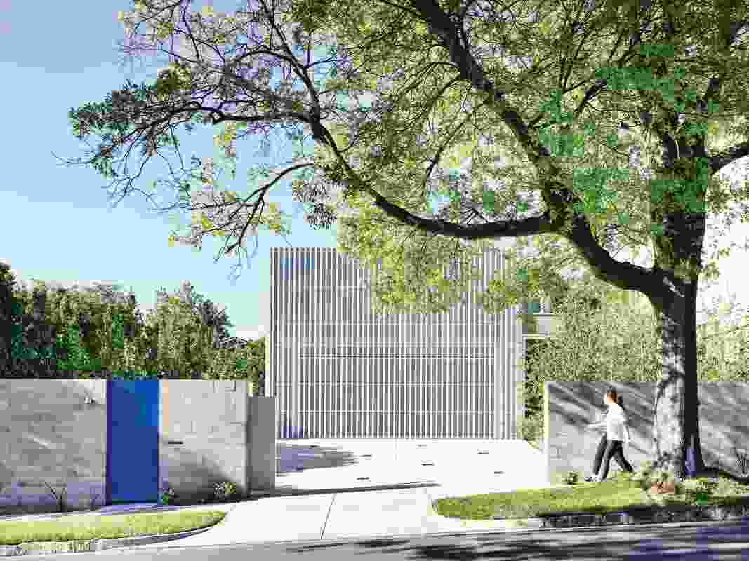 A white metal grille and dramatic blue gate conceal what's inside and define the exterior of the dwelling.