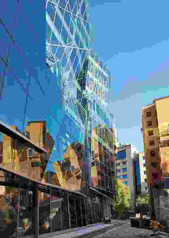 The angular glass shards of the western facade reflect the building's busy surroundings.