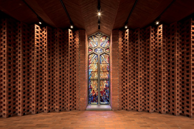 The folded brick screen behind the baptismal font incorporates a salvaged stained-glass window.